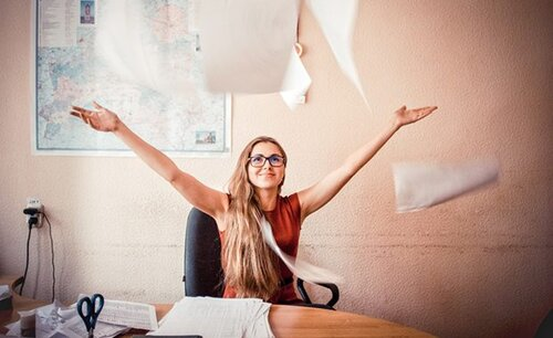 A picture of a professional woman in marketing throwing papers in the air.
