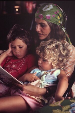 A picture of a mother holding her two children, reading to them from a book.