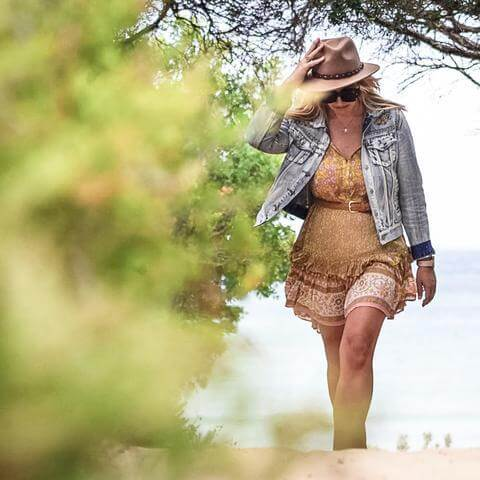 Bianca White from ECO & BASICS walking on a beach.