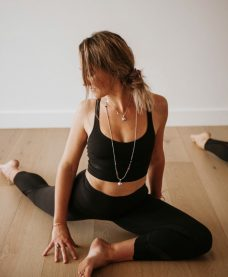 A yoga teacher leading a class wearing black workout clothing and necklaces.