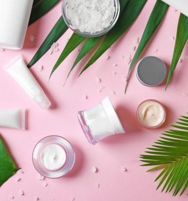 On a pink background various beauty products are placed over palm and monstera leaves, showcasing an example of digital marketing for Beauty PR agencies in Sydney.