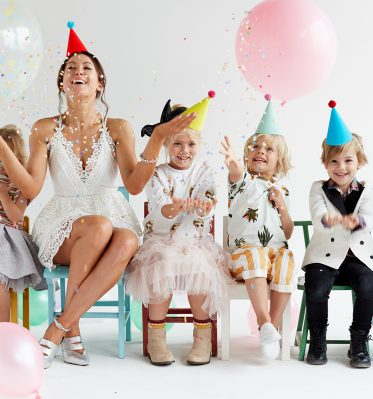Five children and one woman site together in a row of colorful chairs with balloons and confetti thrown around, showcasing some of the unique creative content made for kids marketing strategies.