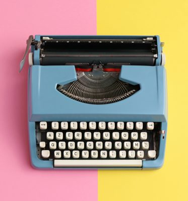 Blue typewriter is placed over a pastel pink and yellow background ready to be used for copy writing.